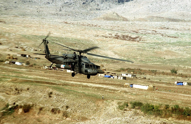 A U.S. Army Black Hawk flies over a small village in the Kurdish occupied security zone in Northern Iraq during OPC